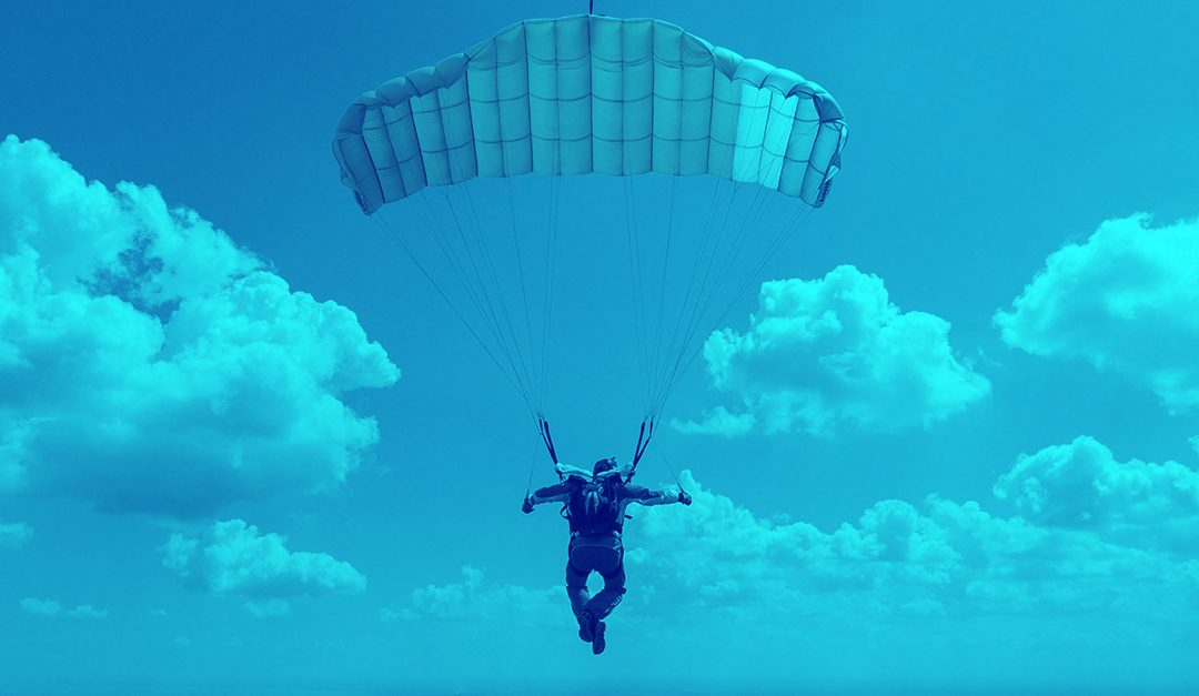 man parachuting in the clouds