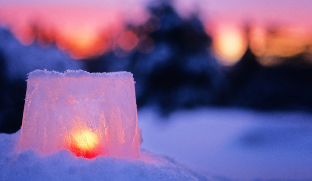 Glowing ice candle on winterscape