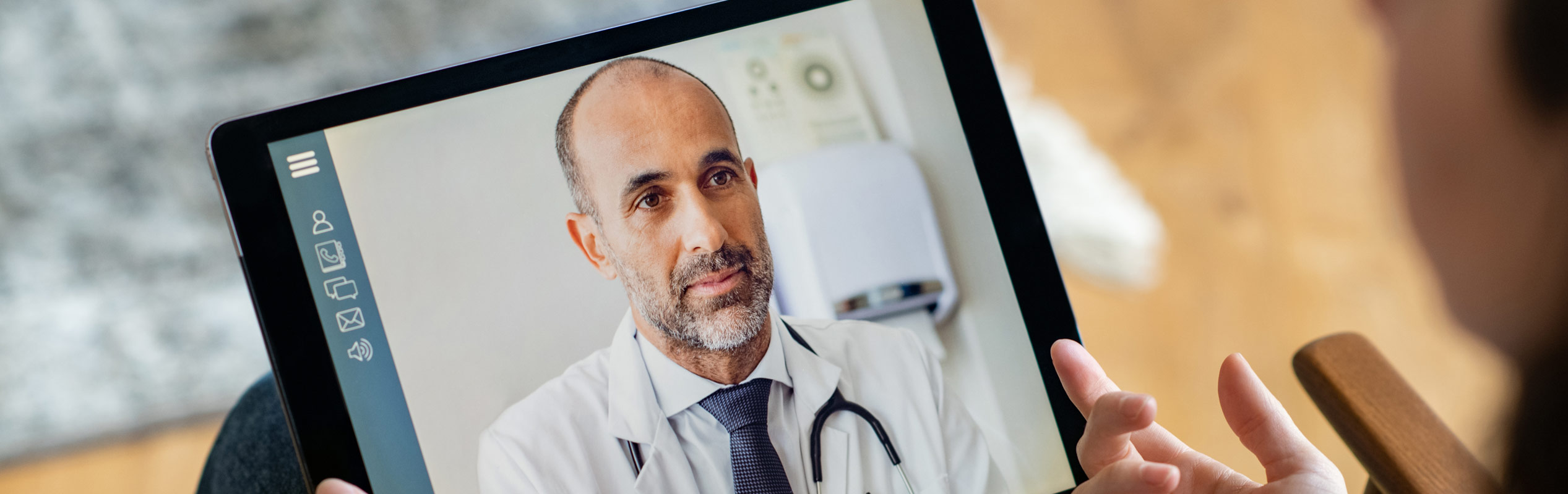 Person talking to their doctor through a tablet