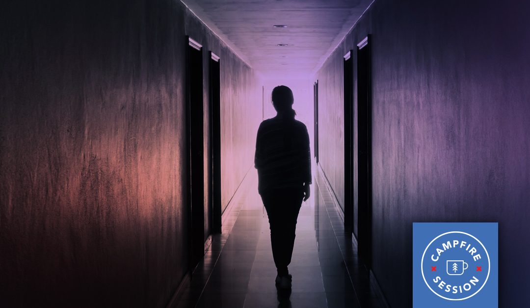 Woman walking down dark hallway