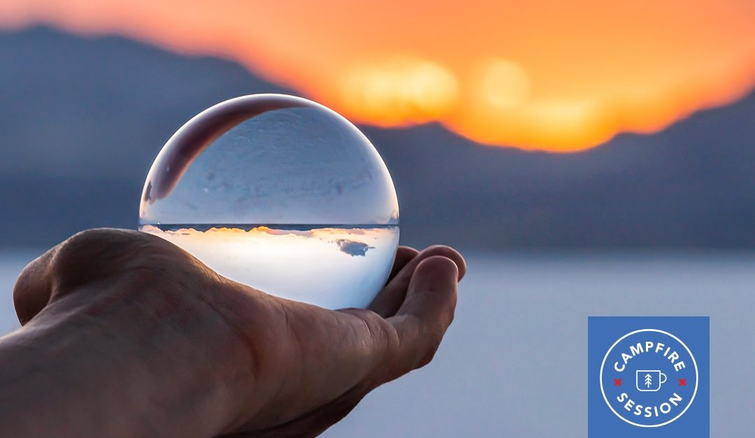 Glass bubble in hand in front of sunset